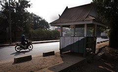 A motorcyclist rides past the police checkpost where Sombath Somphone was kidnapped in Vientiane a year ago.(AP Photo)